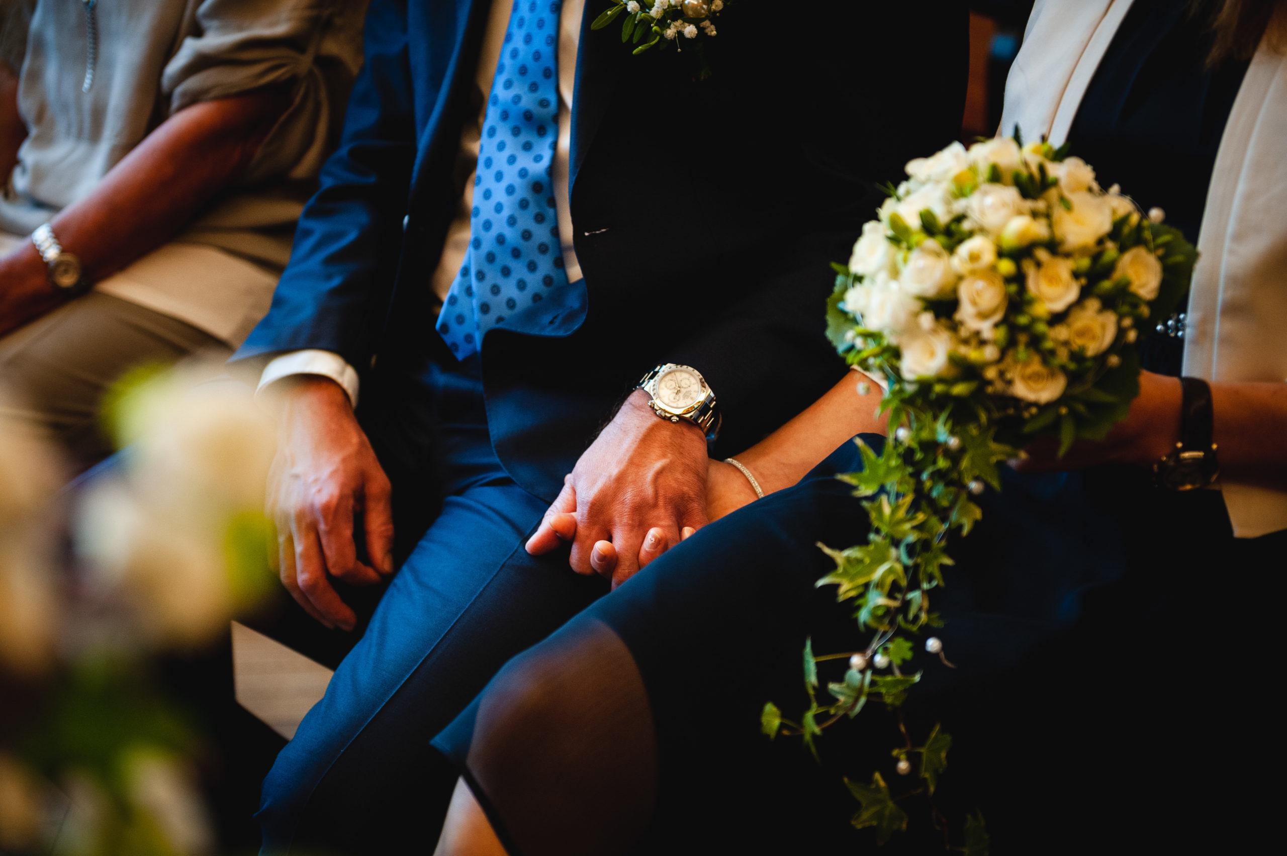 Detailbild, Braut und Bräutigam halten sich die Hände, Brautkleid sichtbar