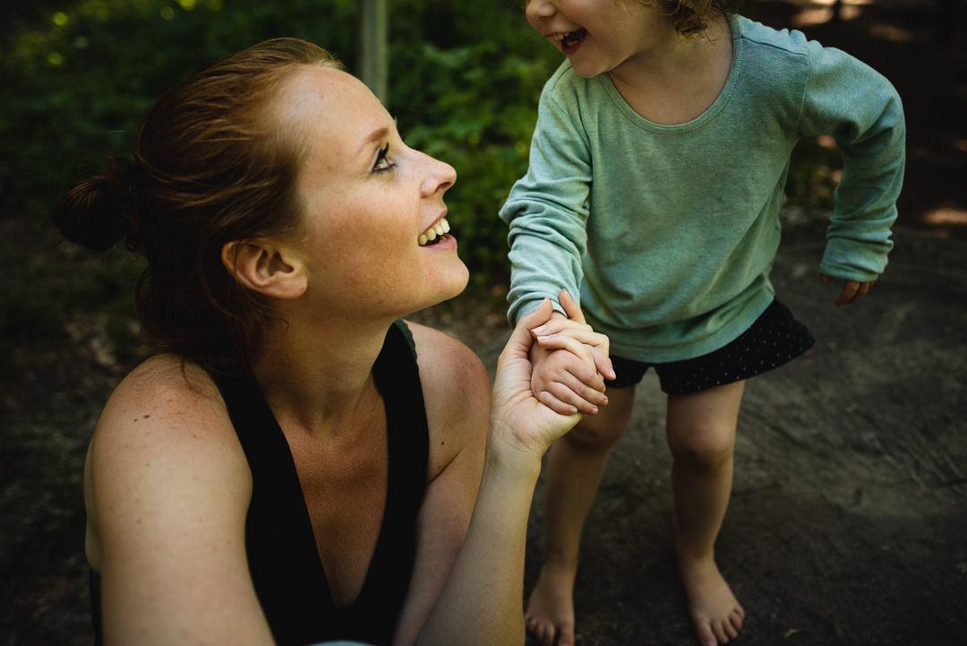 Mutter und Tochter im Wald, schauen sich ins Gesicht, die Mutter hält die Hand der Tochter