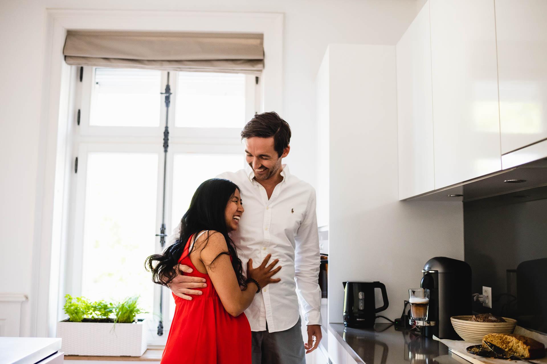 Schwangere Frau in einem roten Kleid umarmt ihren Partner in der Küche