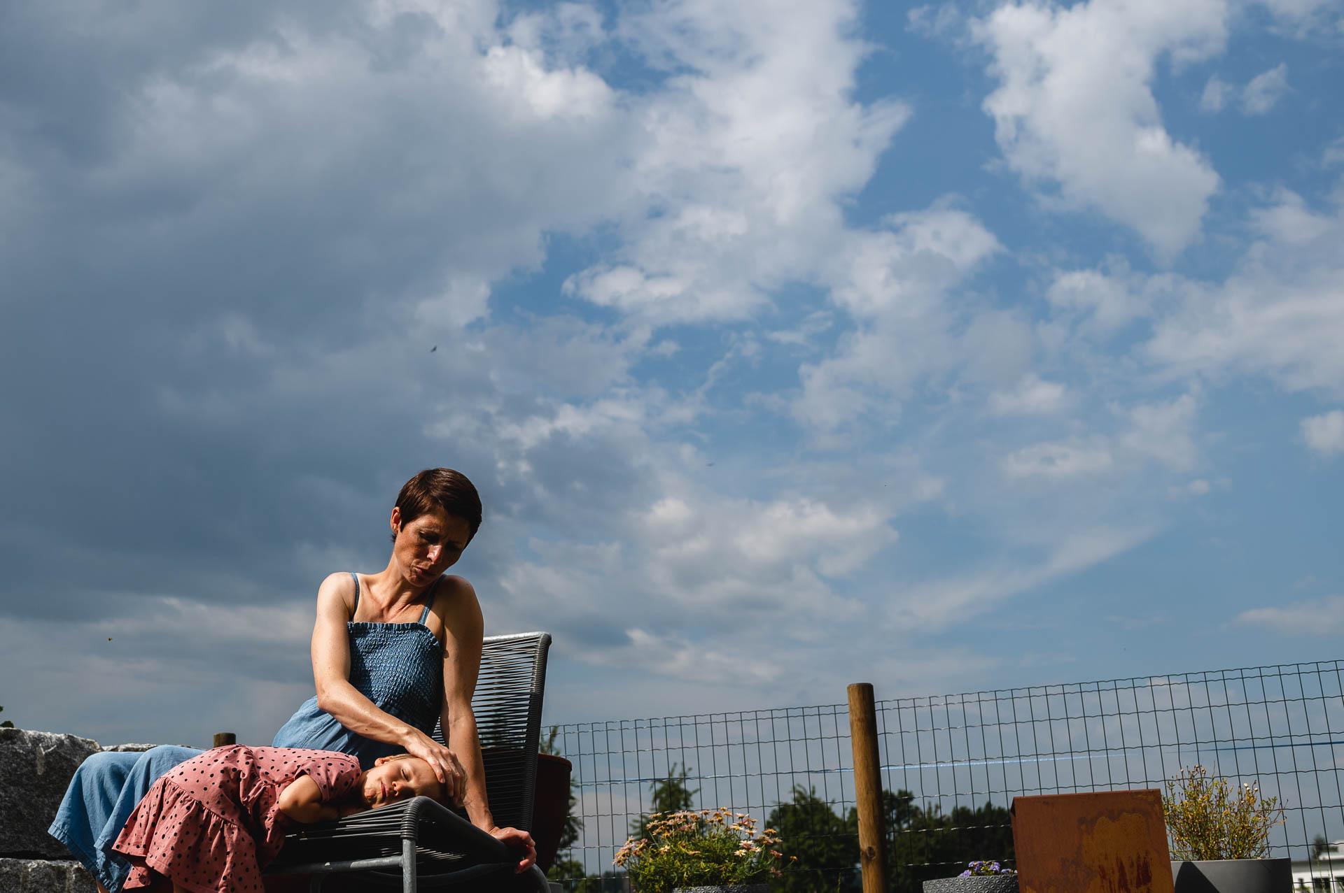 Mutter streichelt Tochter im Gesicht, sie liegt auf dem Stuhl neben der Mutter, der blaue Himmel mit weissen Wolken ist im Hintergrund