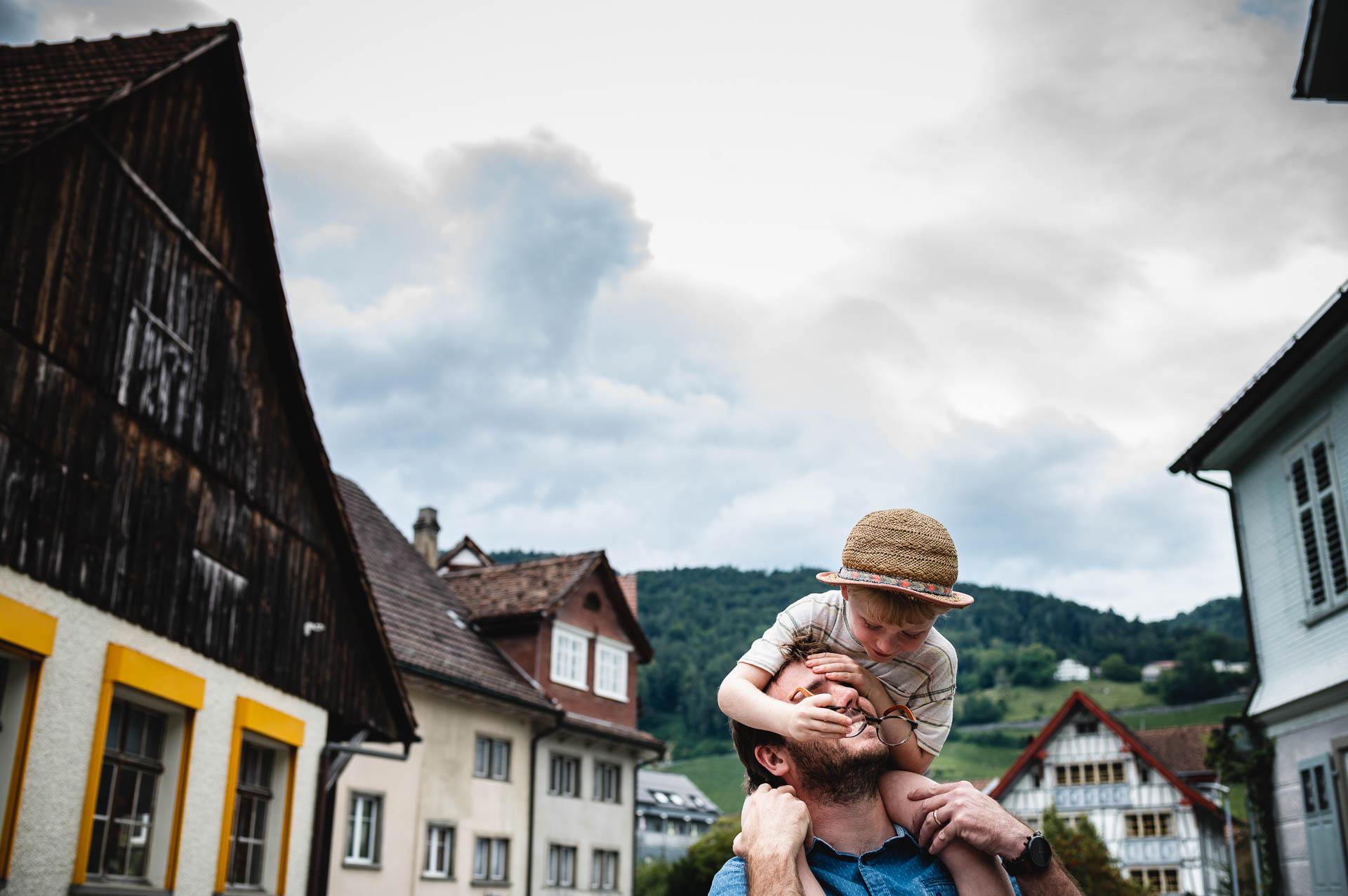 Kind auf den Schulter seines Vater klaut seine Brille, Dorfhäuser und Berge im Hintergrund