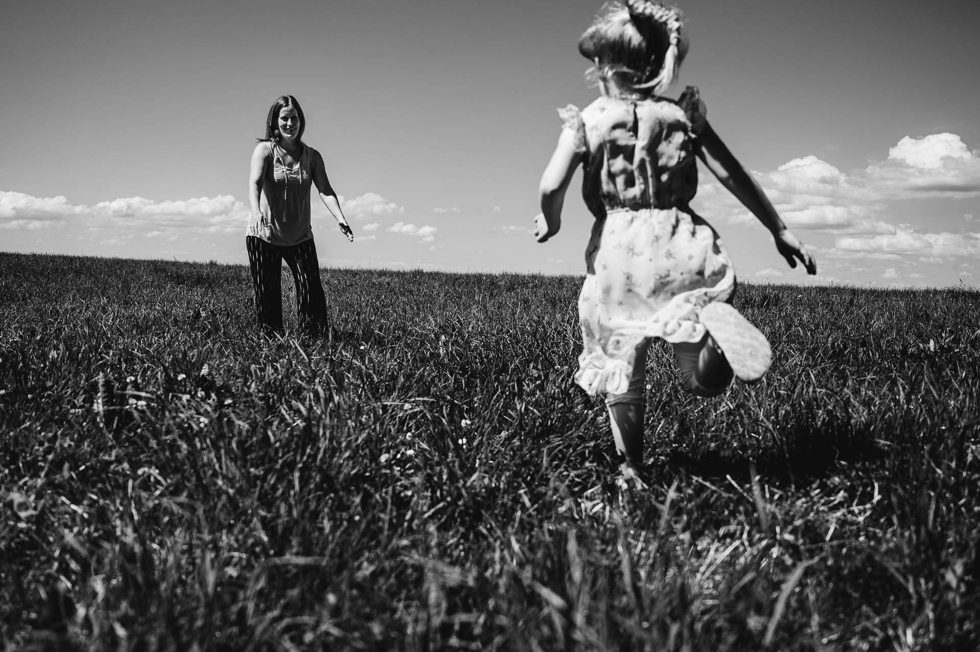 Mädchen rennt auf der Wiese zu ihrer Mutter, die sie mit offenen Arme empfängt
