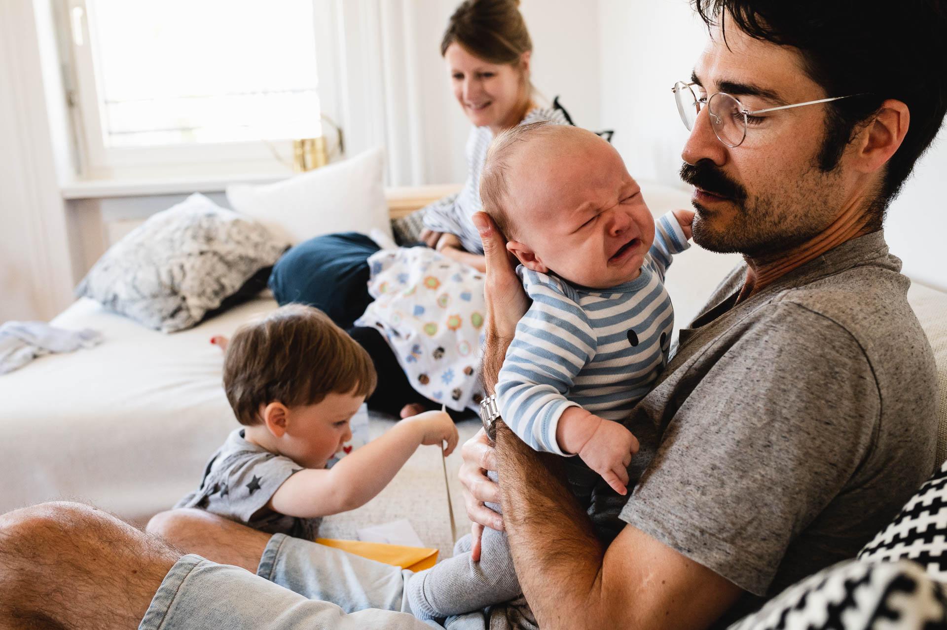 Vater sitzt auf dem Sofa und hält sein Baby, das weint, grösserer Bruder spielt im Hintergrund und Mutter lacht