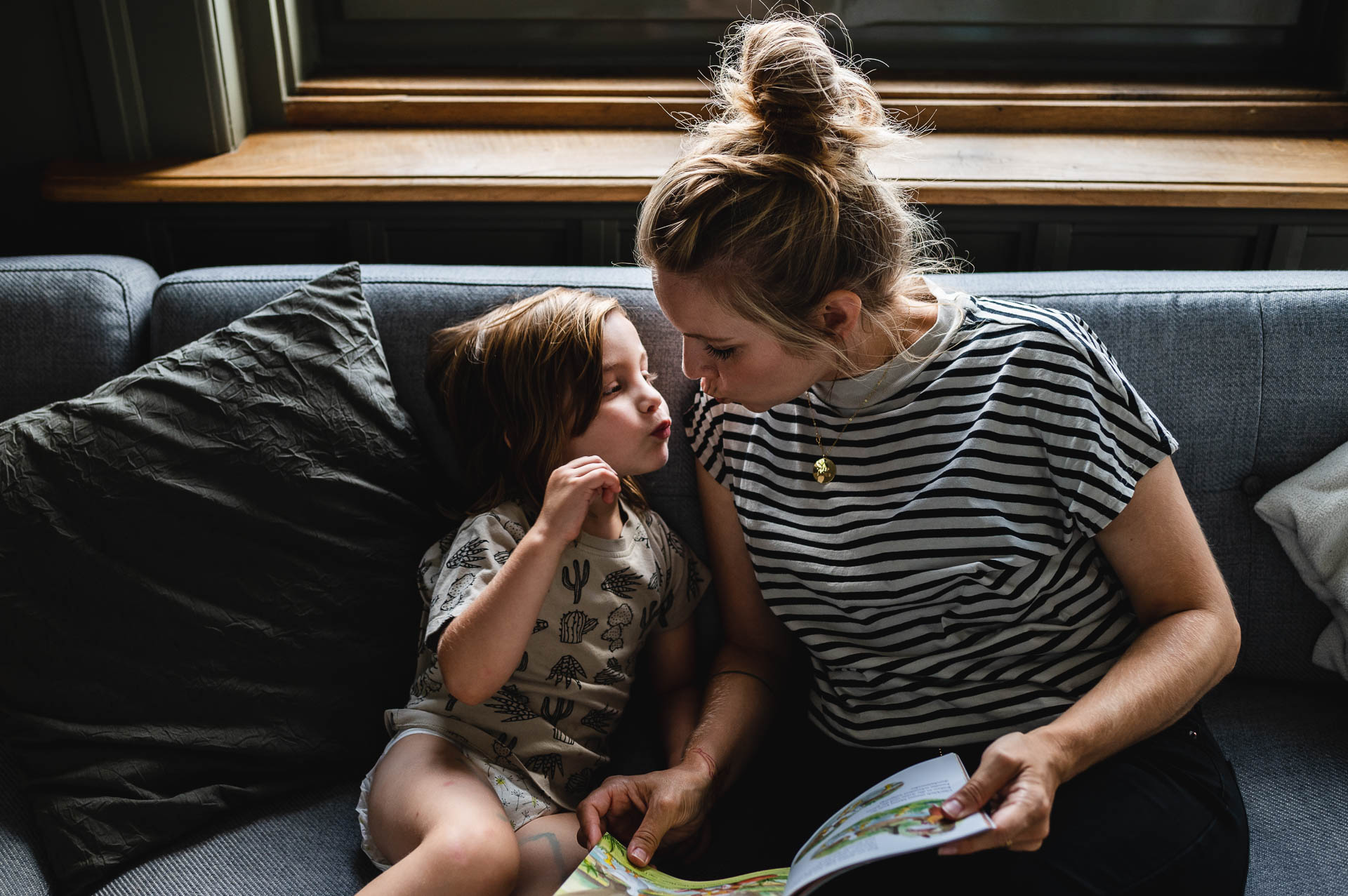 Mutter und Sohn auf dem Sofa geben sich ein Kuss
