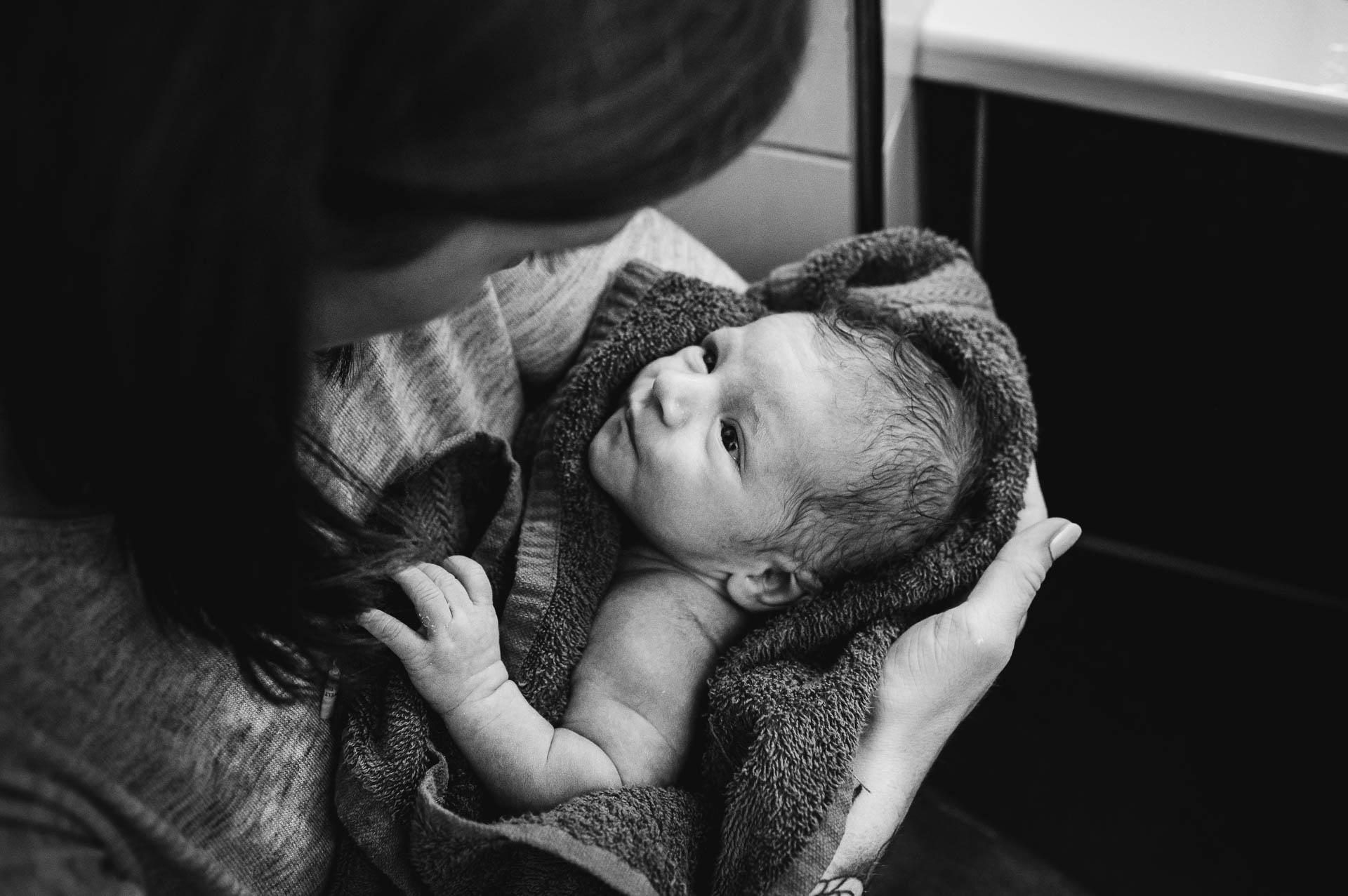 Mutter hält sein Neugeborenes Baby in den Armen in einem Badetuch, das Baby schaut zu ihr
