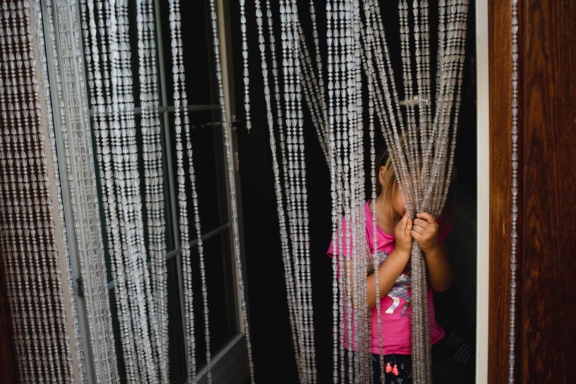 Mädchen versteckt dich hinter einem Perlenvorhang