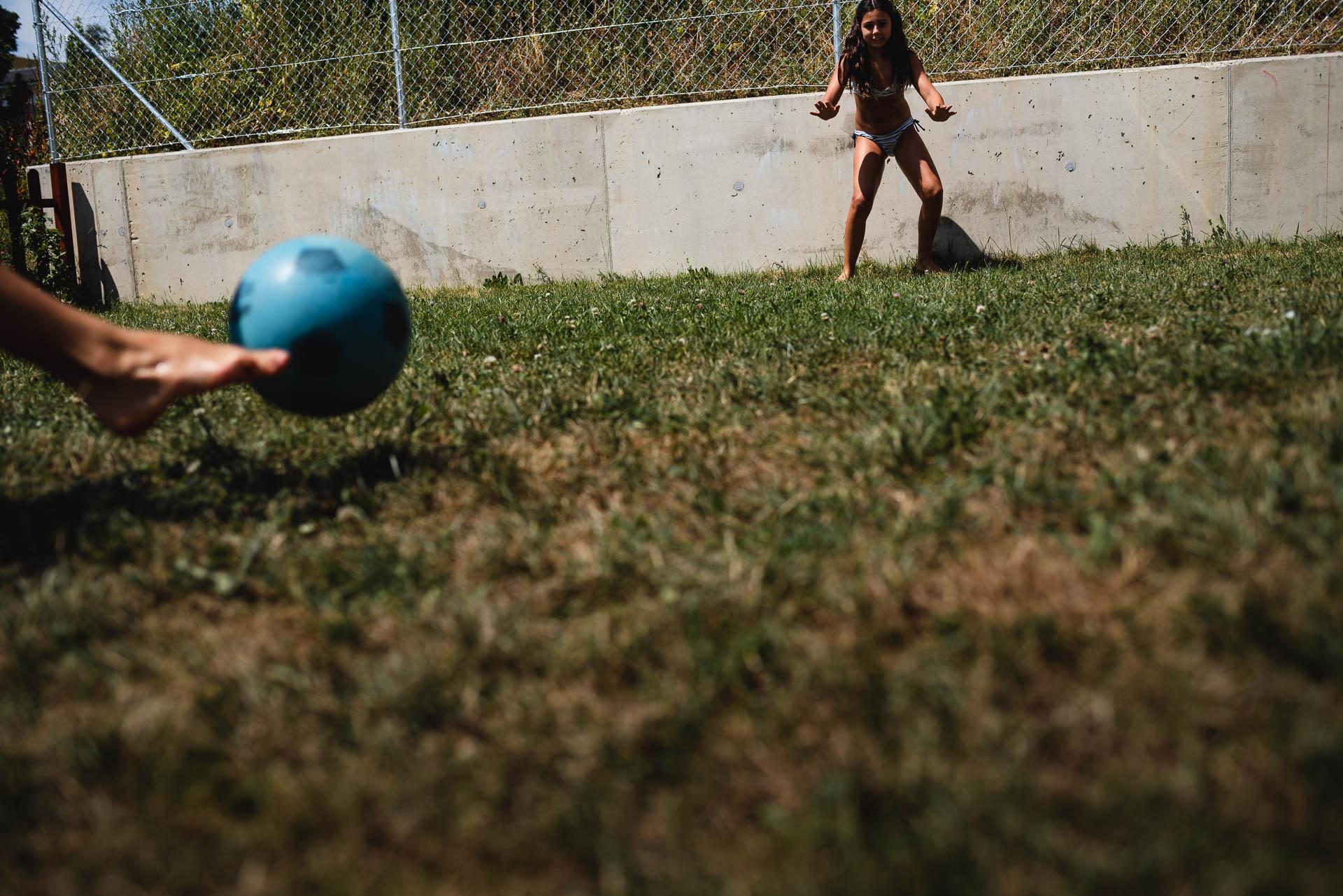 Zwei Teenager spielen Fussball auf der Wiese, im Vordergrund der Fuss vom einem, der den Ball wirft, im Hintergrund das Mädchen, das auf den Ball gespannt wartet